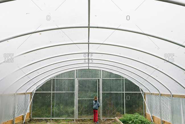 Boy opening door to large greenhouse