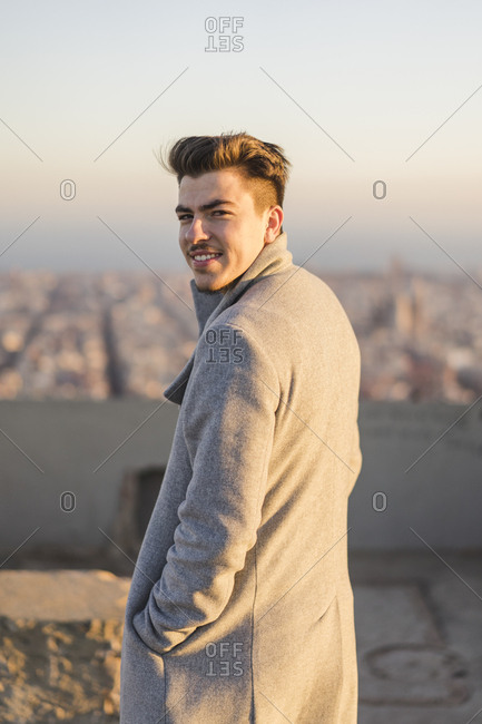 Portrait of smiling young man wearing grey coat at sunset