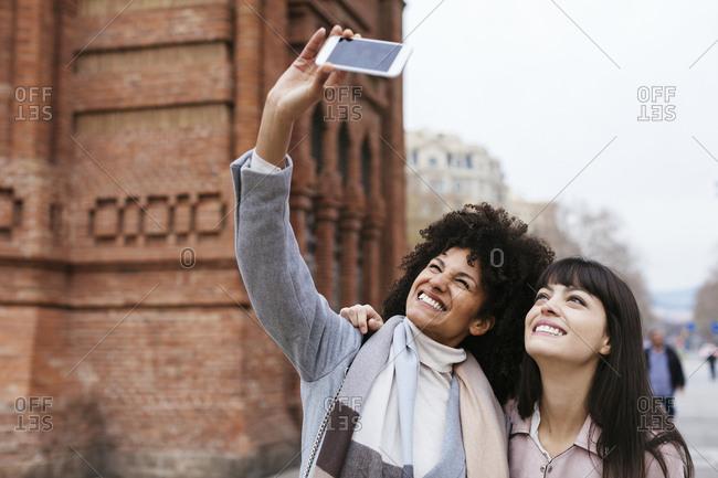 Spain- Barcelona- two happy women taking a selfie at a gate