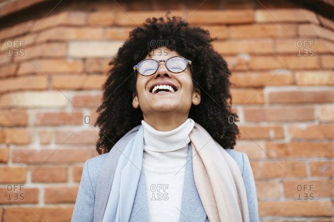 Portrait of laughing woman at brick wall