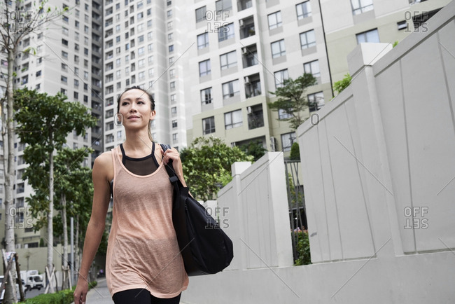 Confident fit woman walking in urban environment