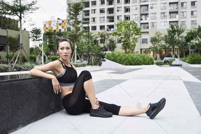 Fit woman relaxing after exercising in urban environment