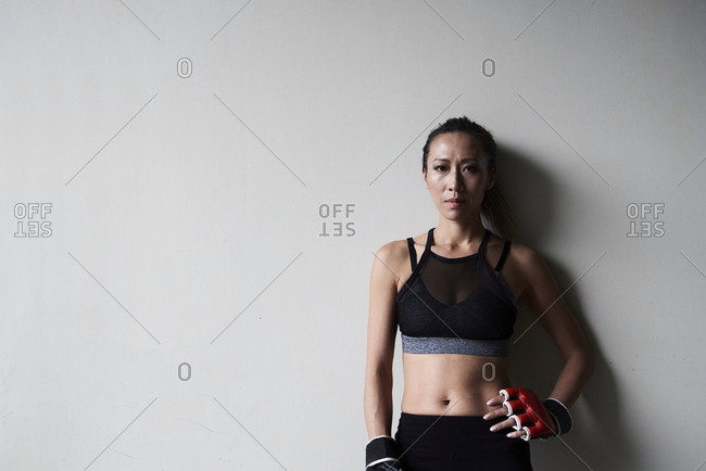 Portrait of confident female boxer against grey wall