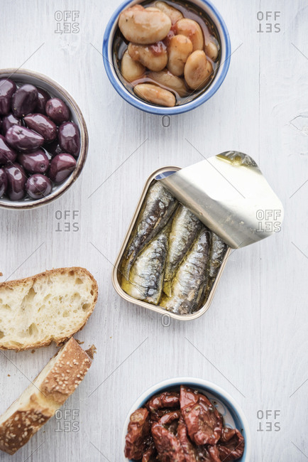 Tin can of sardines in oil- bowls of pickled vegetables and slices of bread