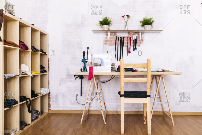 Workspace with sewing machine on table in studio