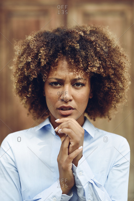 Portrait of serious woman with afro hairstyle outdoors