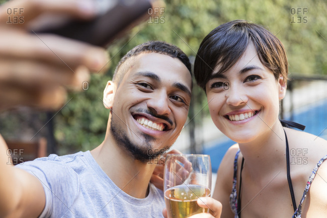 Smiling young couple having a beer and taking a selfie outdoors