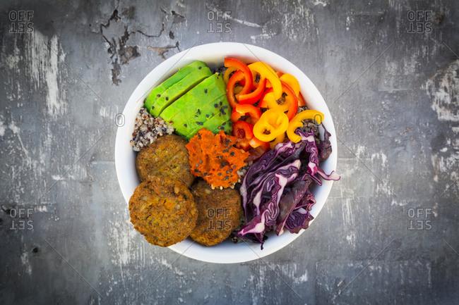 Quinoa-Buddha-Bowl with paprika- avocado- red cabbage- quinoa- quinoa patty- ajvar and black sesame