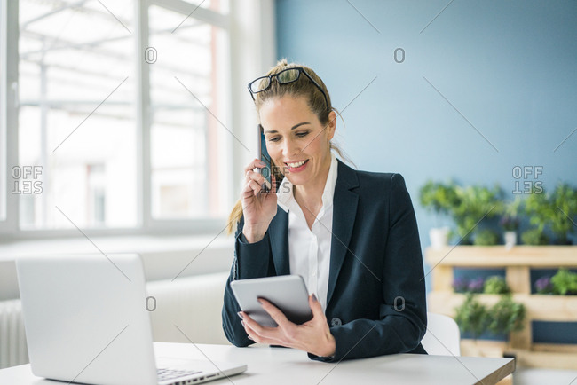 Businesswoman sitting at desk- talking on the phone- looking at digital tablet