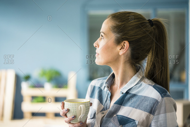 Woman refurbishing her new home- taking a break- drinking coffee