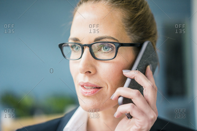 Successful businesswoman standing at home- talking on the phone
