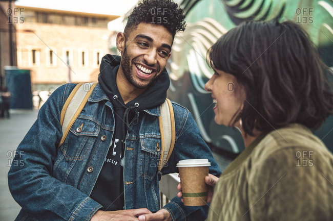 Happy young man and woman with coffee talking in the city