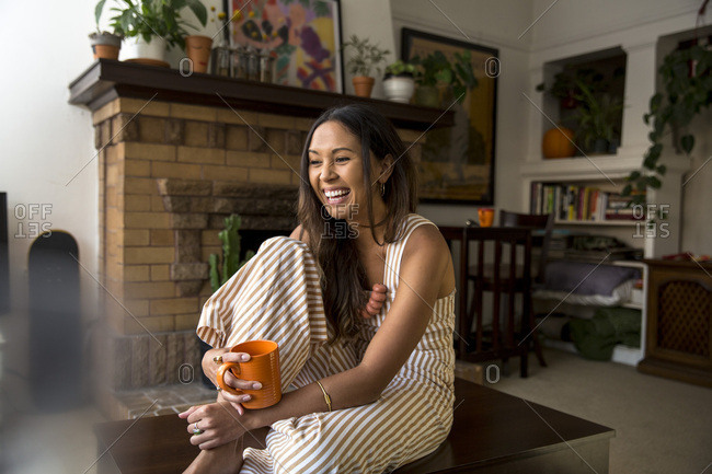 Laughing young woman with coffee mug sitting at home