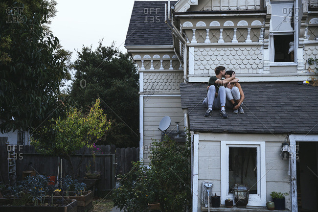 Couple sitting on roof kissing