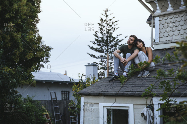 Relaxed couple sitting on roof