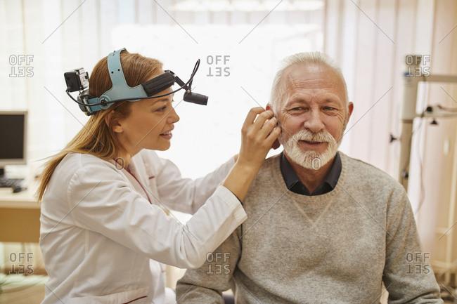 ENT physician examining ear of a senior man