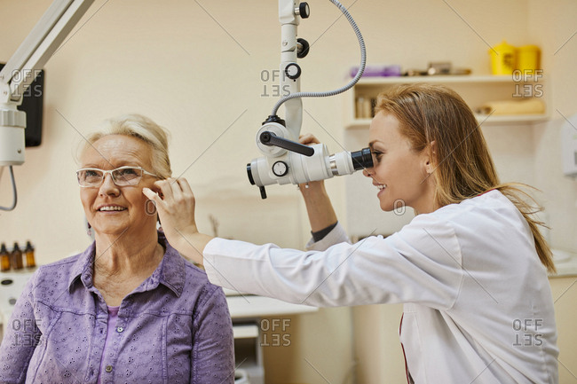 ENT physician examining ear of a senior woman