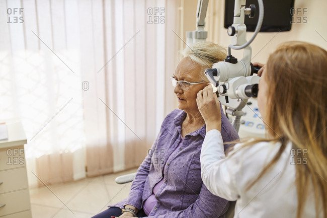 ENT physician examining ear of a senior woman