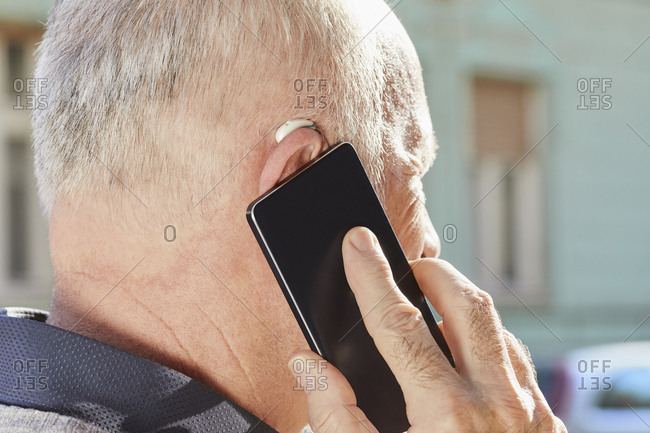 Close-up of senior man with hearing aid using smartphone