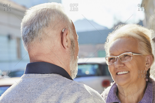 Close-up of senior man with hearing aid talking to senior woman