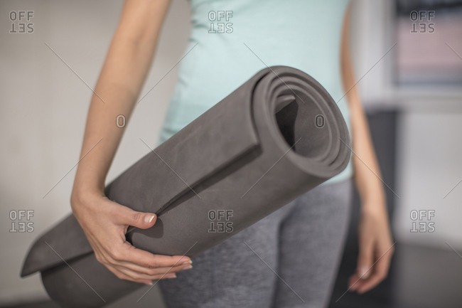 Close-up of woman carrying yoga mat in studio