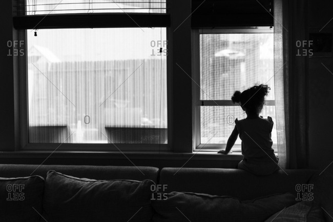 Silhouette of curly haired child looking out window