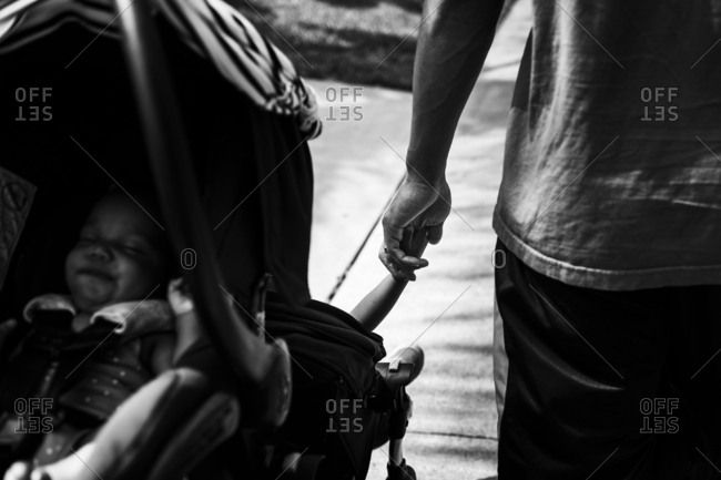 Father holding hands with kid in a stroller while on a walk