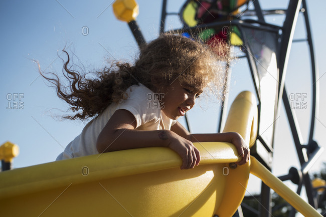 Little girl looking over edge of yellow slide