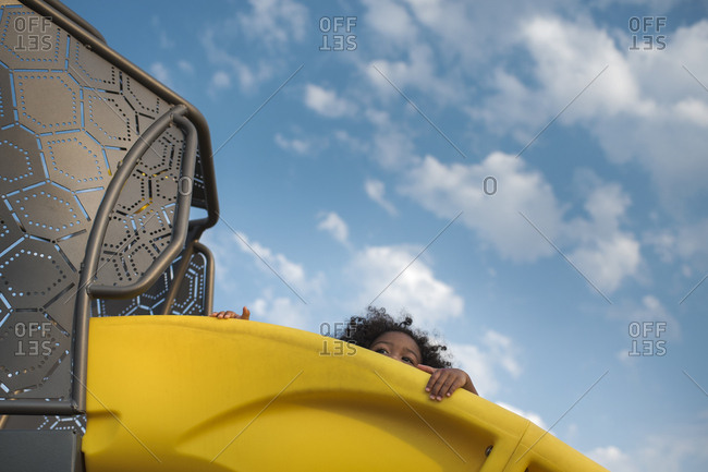 Low angle view of little girl looking over edge of yellow slide