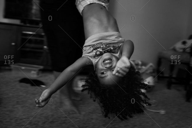 Parent spinning little girl upside down