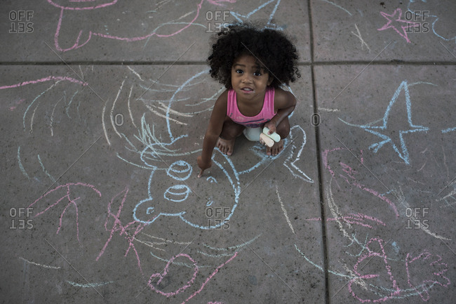 Little girl drawing on sidewalk with chalk