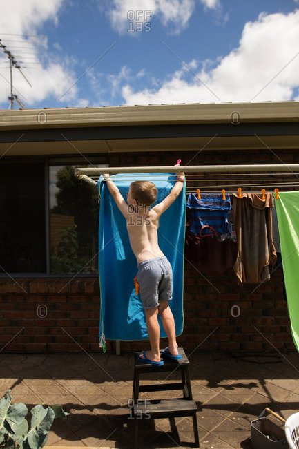 Boy hanging towel on clothesline