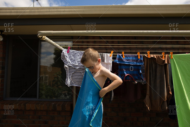 Boy wrapping towel around himself next to clothesline