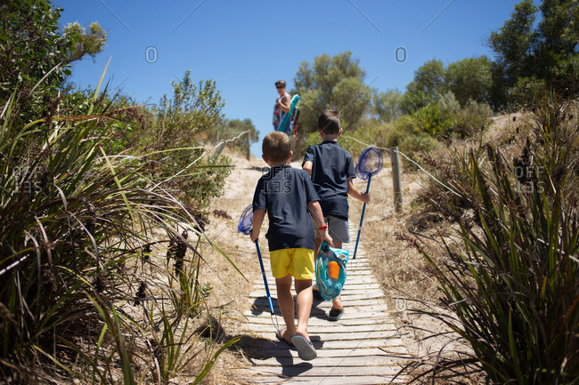 Two boys holding nets walking together on footpath toward beach