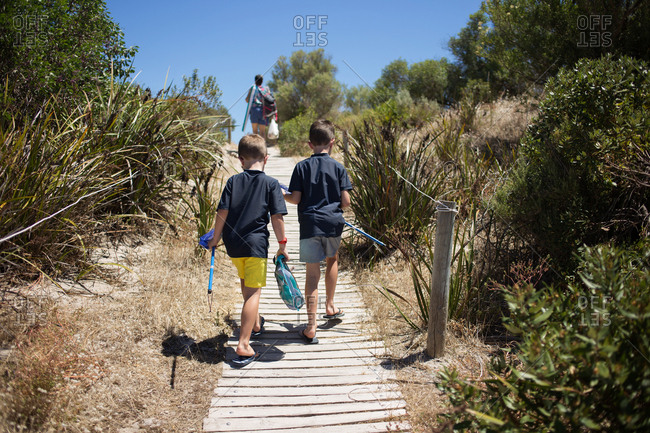 Two boys walking together on footpath towards the beach