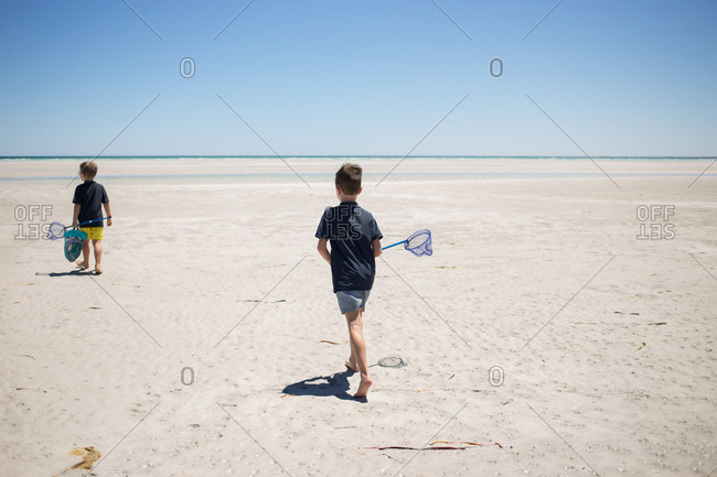 Two boys carrying nets walking on a sandy beach