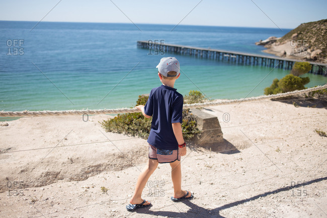 Boy walking along path leading to the ocean