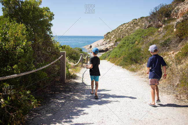 Two boys walking on footpath toward the ocean