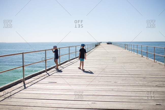Two boys on an empty pier looking over at the water