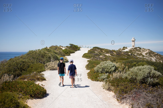 Two boys walking together on path toward lighthouse