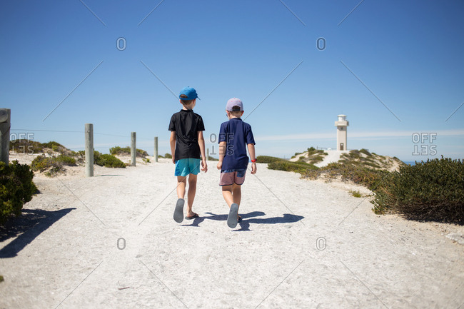 Two boys walking together toward lighthouse
