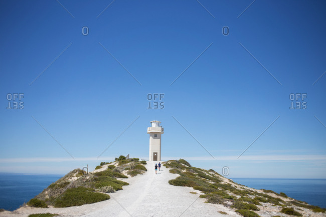 Two people hiking toward lighthouse at top of coastal headland