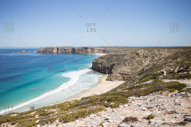 Scenic view of cliffs along sandy beach
