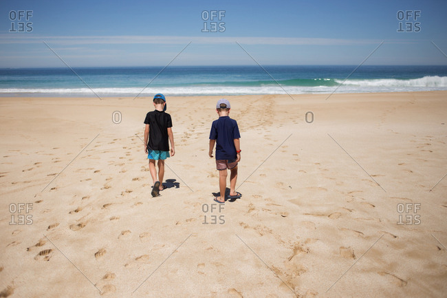 Two boys walking together on sandy beach