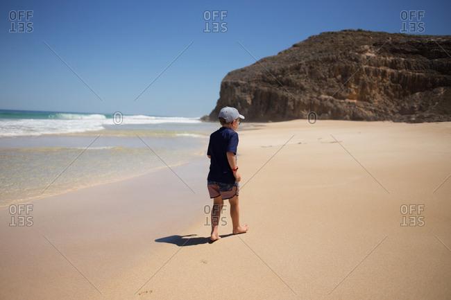 Boy walking barefoot on sandy beach