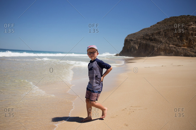 Boy standing on a sandy beach as the waves come in
