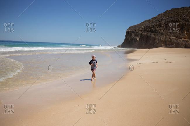 Boy running through the waves on sandy beach