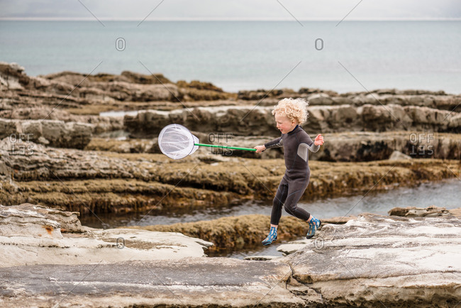 Little boy running with a net on Hawke's Bay, New Zealand
