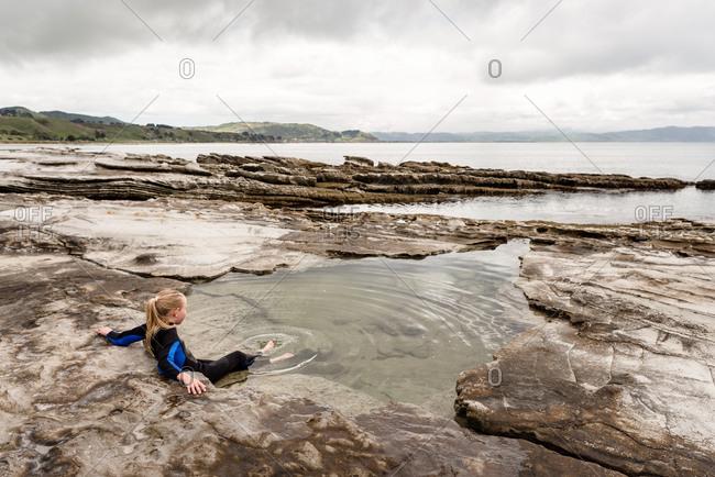 Girl relaxing in a tide pool on Hawke's Bay, New Zealand