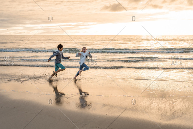 Kids chasing each other on a beach at sunset